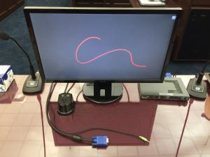 Picture of a laptop at a counsel table with the VGA cable plugged into the evidence presentation system